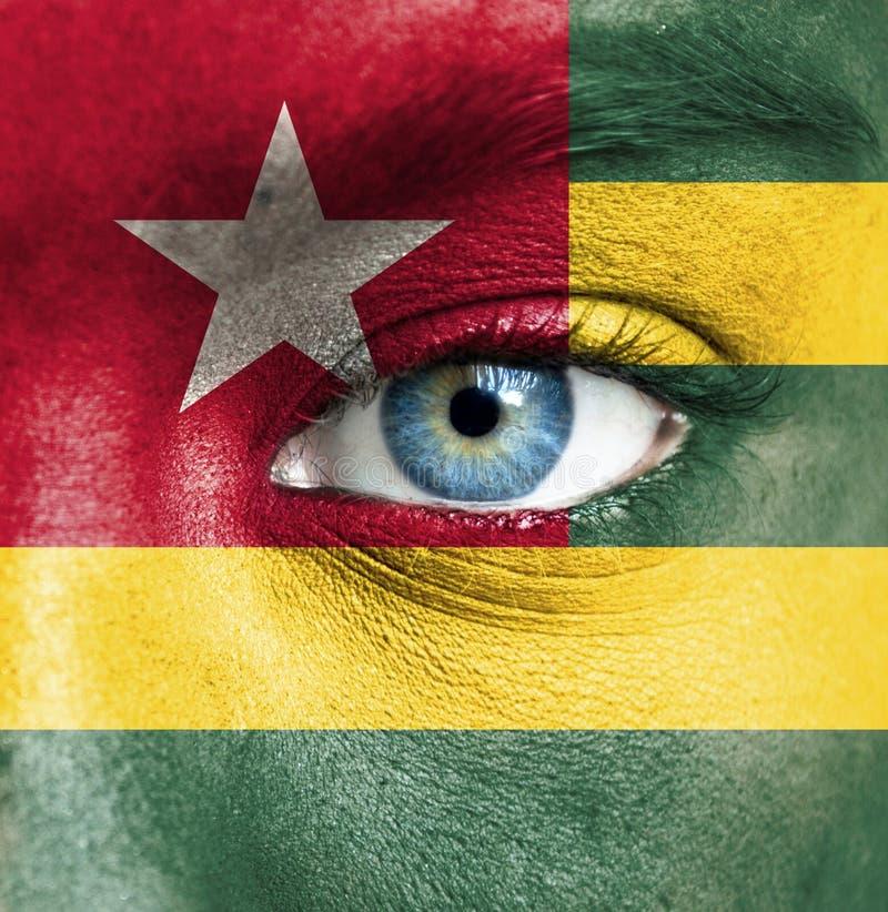 Mänsklig framsida som målas med flaggan av Togo fotografering för bildbyråer