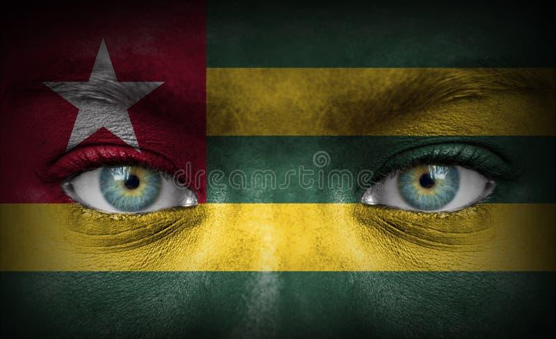 Mänsklig framsida som målas med flaggan av Togo arkivfoton