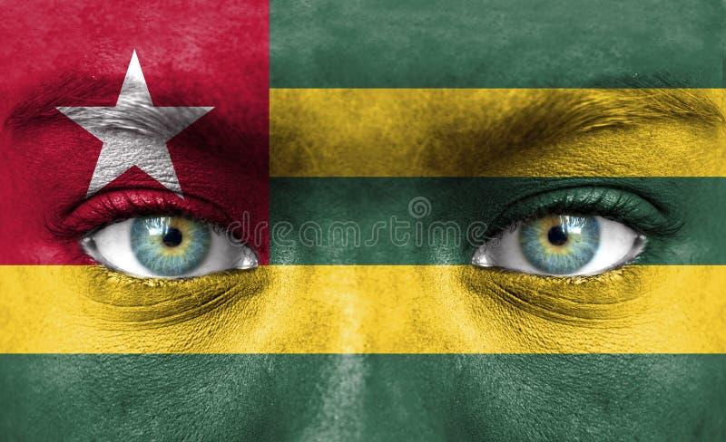 Mänsklig framsida som målas med flaggan av Togo arkivbilder
