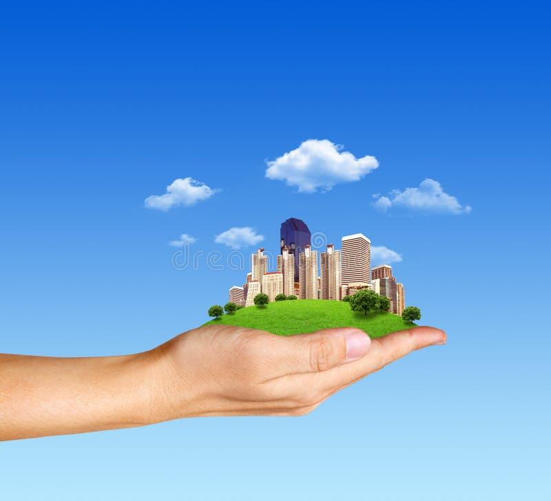Mänsklig hand för begrepp som rymmer en stad på grönt gräs royaltyfri illustrationer