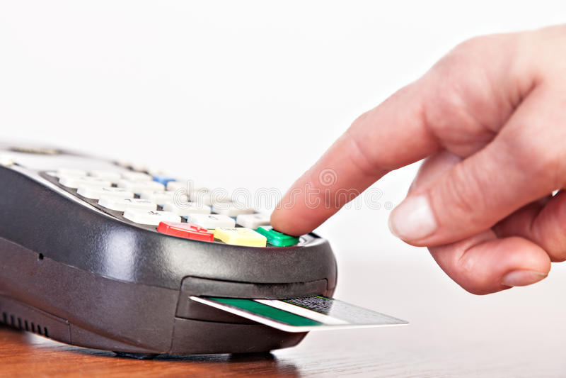 Mänsklig hand genom att använda betalningterminalen, kreditkortavläsare arkivfoto