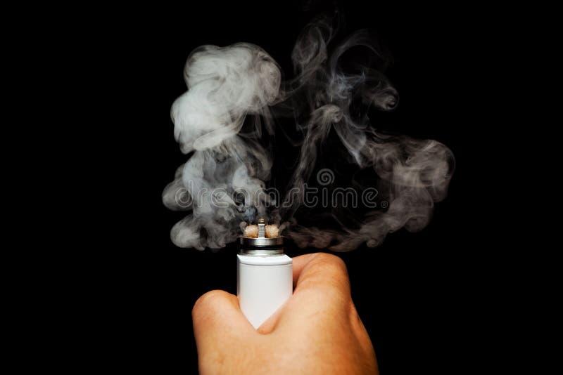 Mänsklig hand som aktiverar den elektroniska cigaretten arkivfoton