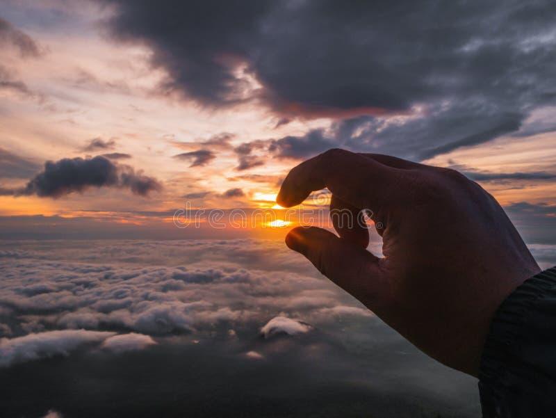 Mänsklig hand som försöker upp hackan solen med härlig soluppgång med idyllisk molnhimmel i morgon på berget royaltyfri bild