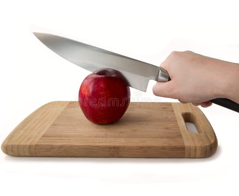 Mänsklig hand som rymmer en kniv och ett rött äpple royaltyfri bild
