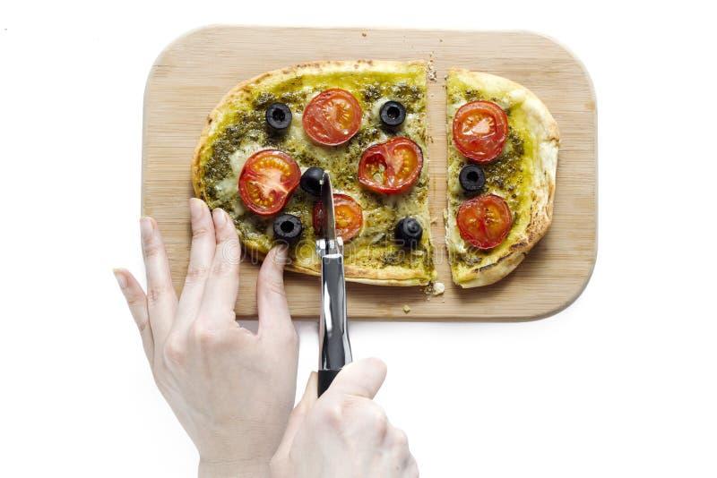 Mänsklig hand som skivar en pizza arkivbild