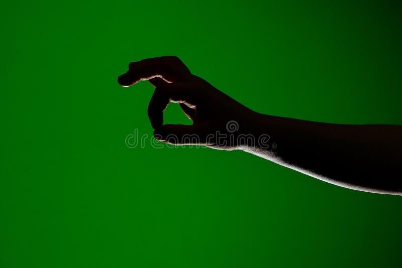 Mänsklig hand, vikt tillsammans för att ta lite litet, isolerat på en röd bakgrund royaltyfri foto