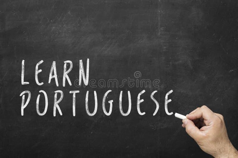 Mänsklig handhandstiltext på svart tavla: Lär portugis royaltyfria foton