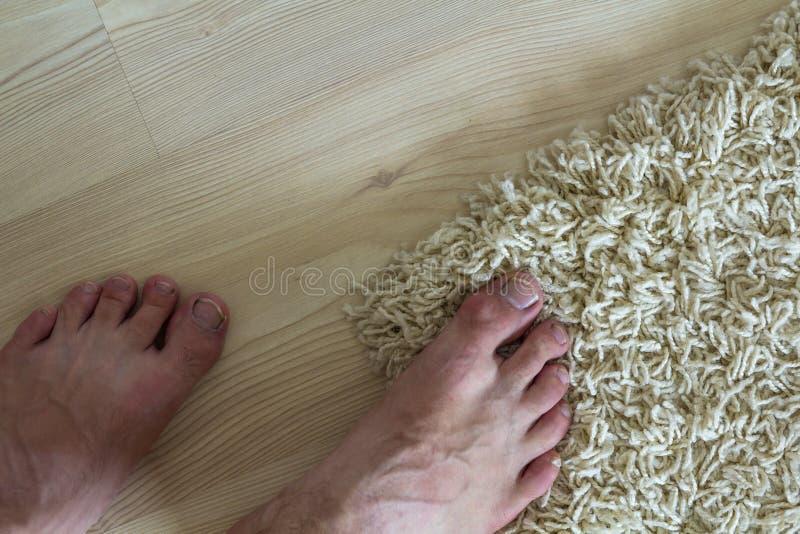 Mänsklig kal fot som står på golvet En fot på matta och royaltyfria bilder
