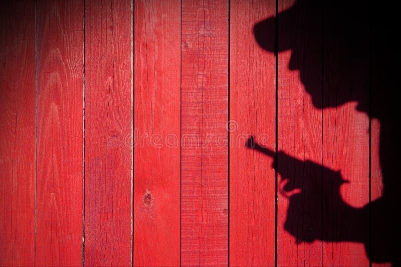 Mänsklig kontur med handeldvapnet i skugga på wood bakgrund, XXXL royaltyfria bilder