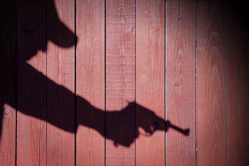 Mänsklig kontur med handeldvapnet i skugga på wood bakgrund, XXXL royaltyfria foton