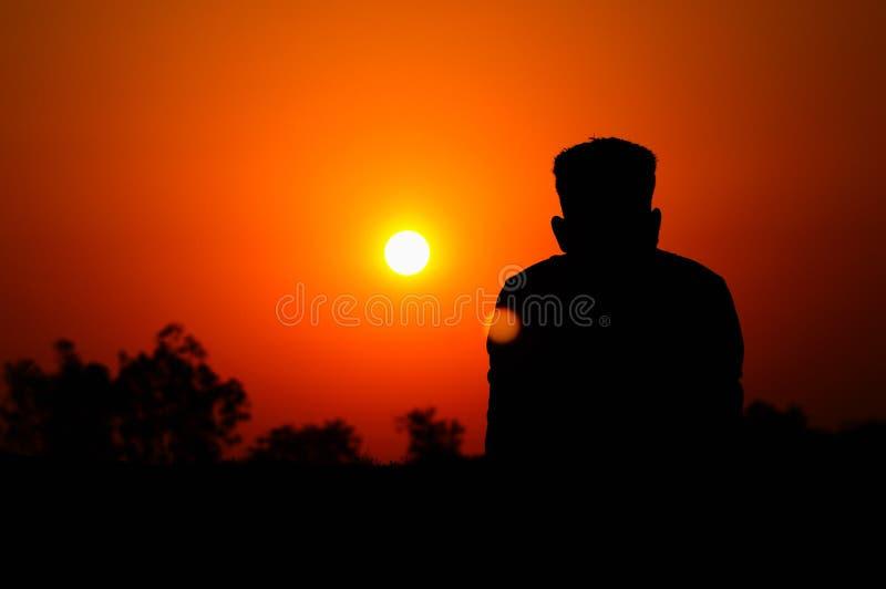 Mänsklig kontur som håller ögonen på inställningssolen, Satara, Maharashtra, Indien royaltyfri bild
