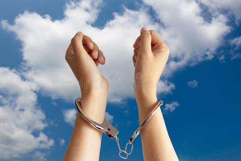 Mänsklig människohandel, slav- arbete och arbets- förtryckproblembegrepp två händer spärrades in av handbojan med blå himmel royaltyfri bild