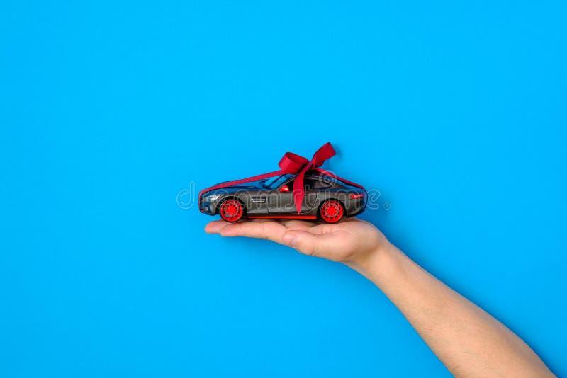 Mänsklig modell för handinnehavbil med ett rött band och pilbåge på blå bakgrund Bilen som gåvan eller gåva, drar bilen,  arkivbilder