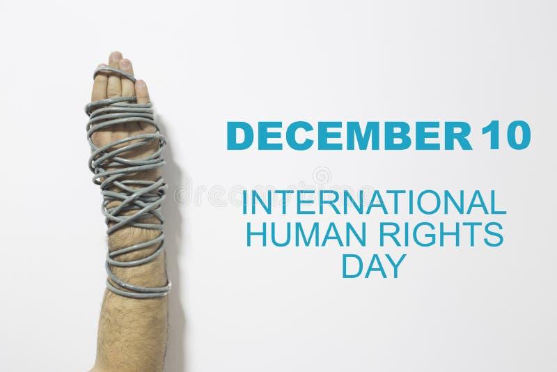 Mänsklig rättighetbegrepp: kedjad fast man mot texten: Skriftlig mänsklig rättighetdag på svart tavla arkivbilder