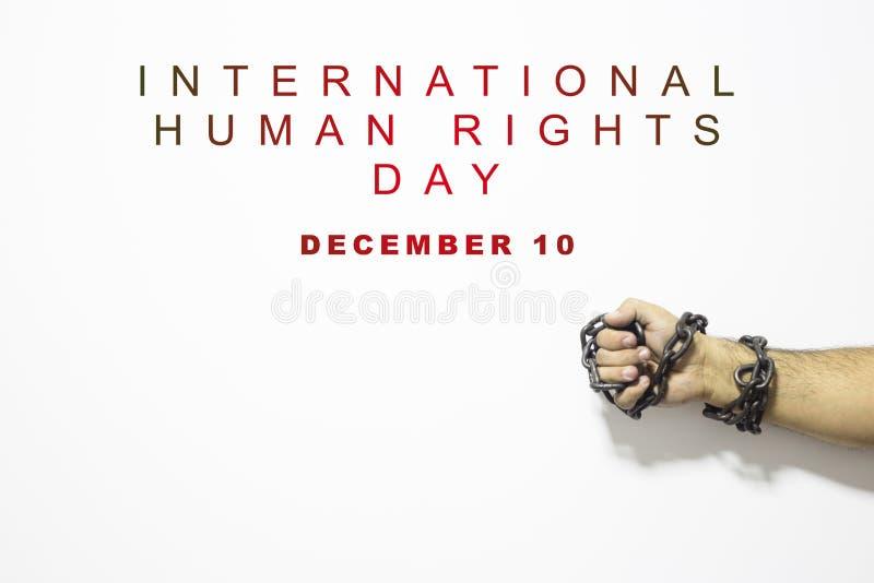 Mänsklig rättighetbegrepp: kedjad fast man mot texten: Skriftlig mänsklig rättighetdag på vit arkivbild