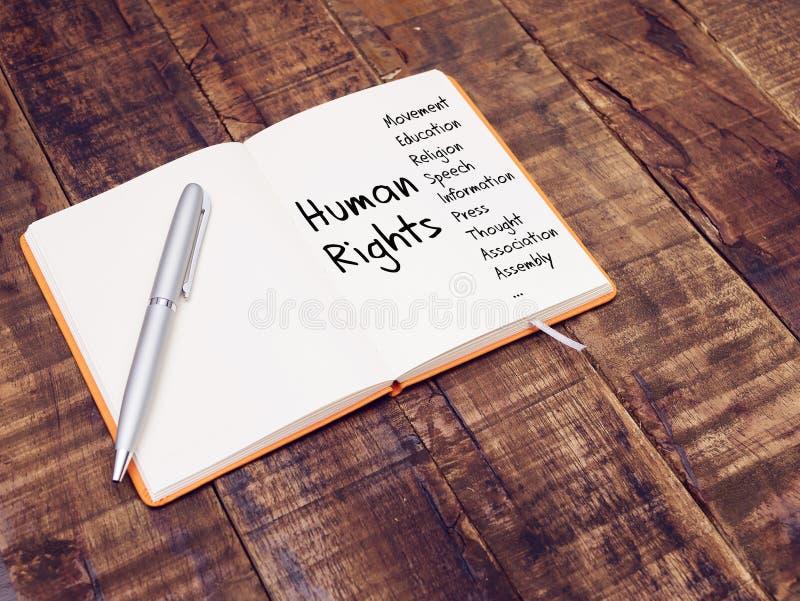 Mänsklig rättighetbegrepp mänsklig rättighetmeningsöversikt med handhandstil på anmärkningsboken på trätabellen royaltyfria foton