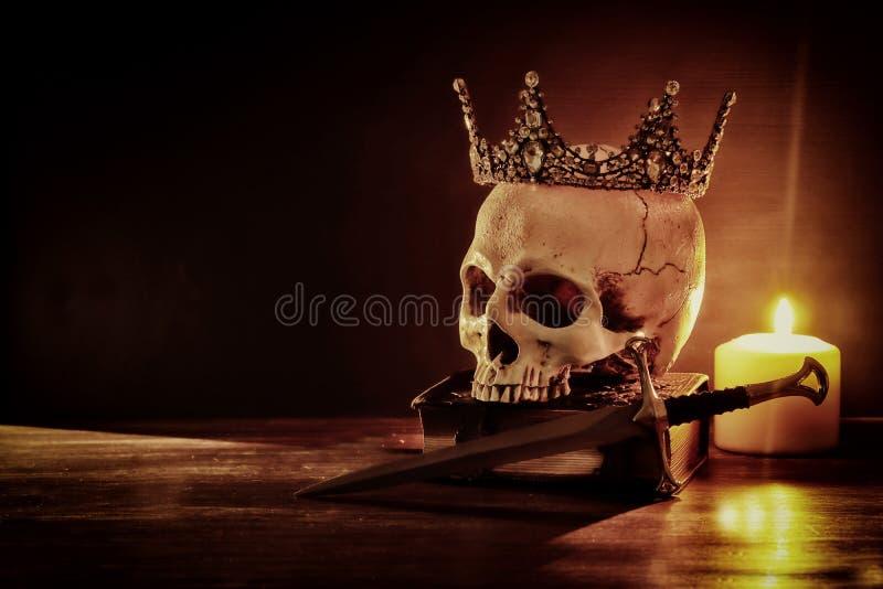 Mänsklig skalle, gammal bok, svärd, krona och bränningstearinljus över den gammal trätabellen och mörkerbakgrund arkivbilder