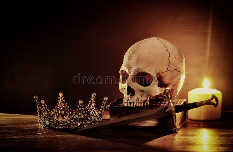 Mänsklig skalle, gammal bok, svärd, krona och bränningstearinljus över den gammal trätabellen och mörkerbakgrund arkivbild