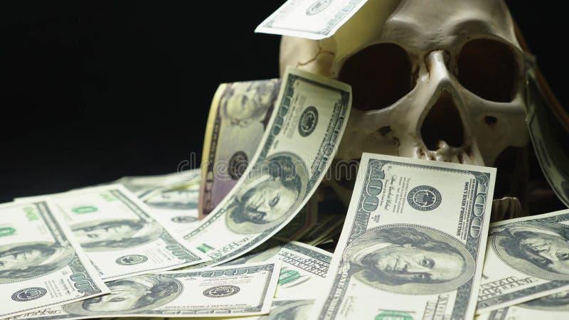 Mänsklig skalle i en hög av amerikansk valuta arkivbilder