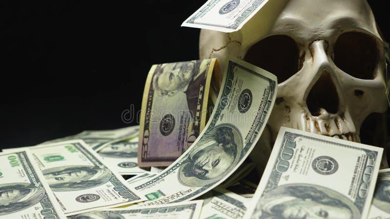 Mänsklig skalle i en hög av amerikansk valuta royaltyfri foto