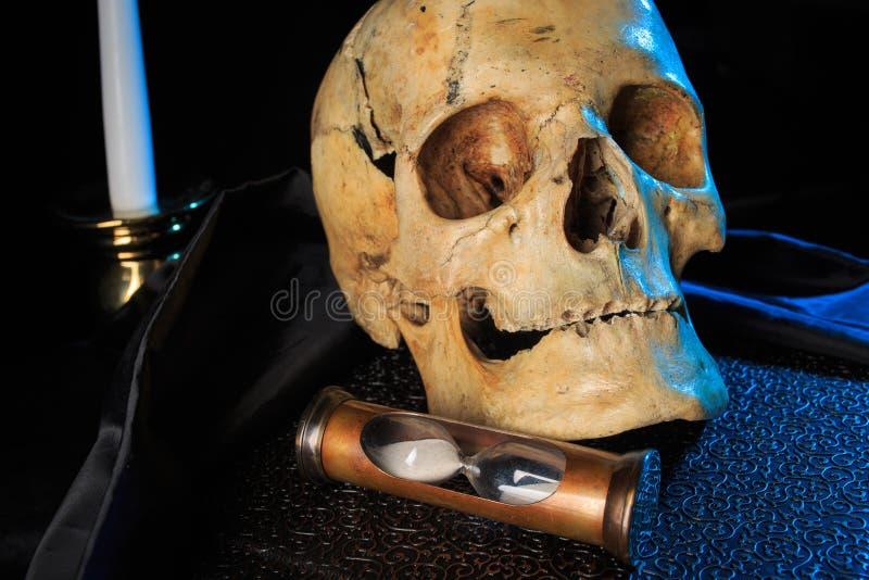 Mänsklig skalle på en bok bredvid klockan Begrepp arkivfoto