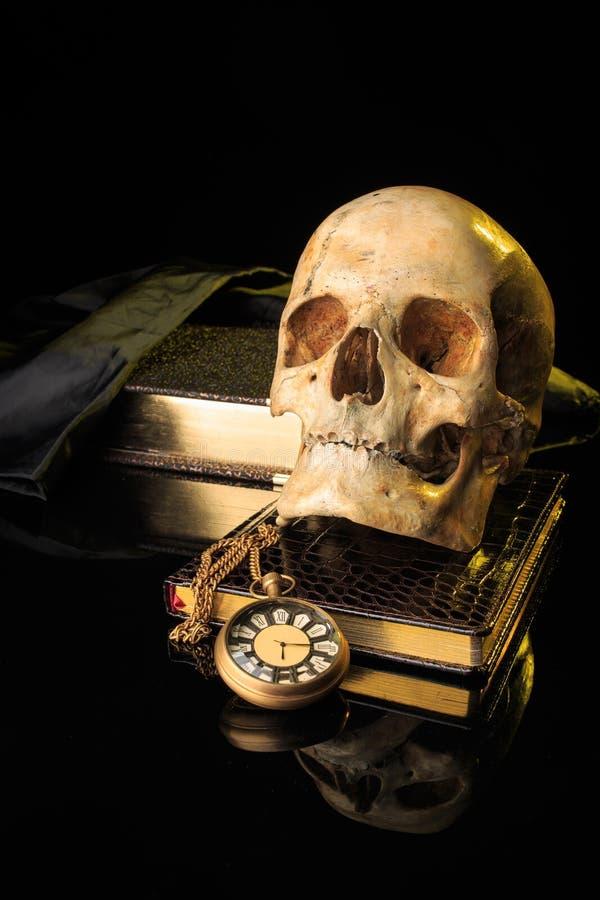 Mänsklig skalle på en bok bredvid klockan Begrepp royaltyfria foton