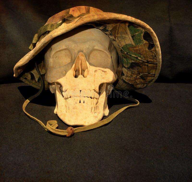 mänsklig skalle som bär en vietnamkrigetkamouflagehatt royaltyfri foto