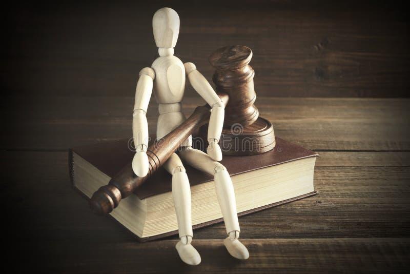 Mänsklig statyett med domare eller auktionsförrättareauktionsklubban Sit On Book royaltyfria bilder