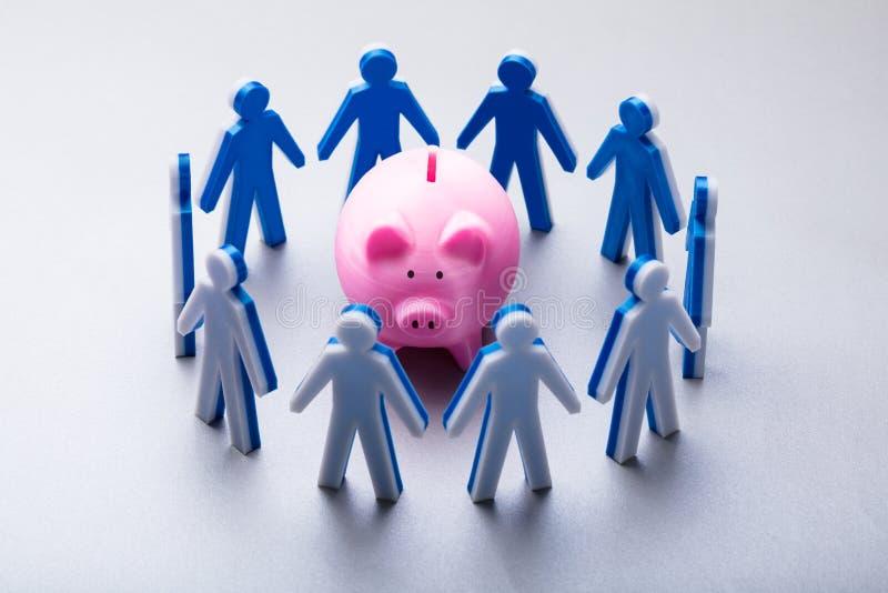 Mänskliga diagram som omger rosa Piggybank royaltyfri foto