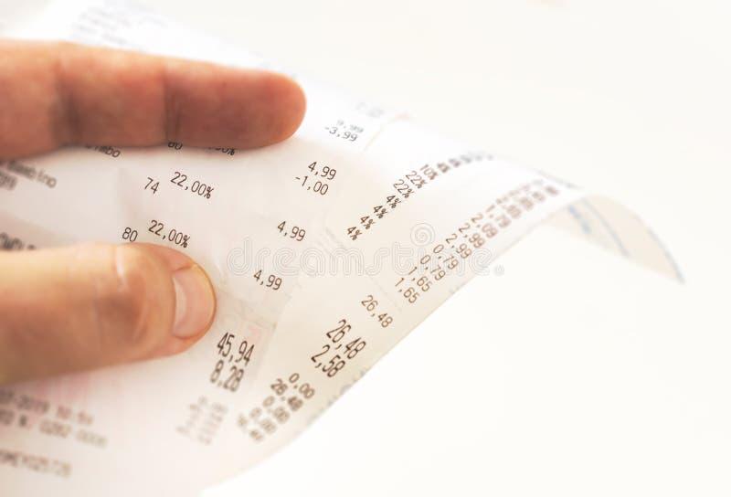 Mänskliga fingrar som rymmer ett pappers- kvitto med räkningen av laddningar och kontrollerar det sammanlagda beloppet royaltyfri bild