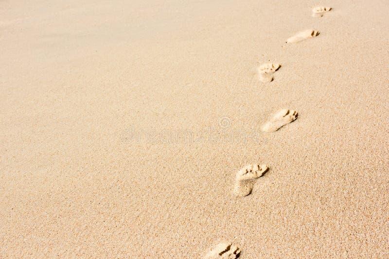 Mänskliga fotspår på strandsand royaltyfria bilder