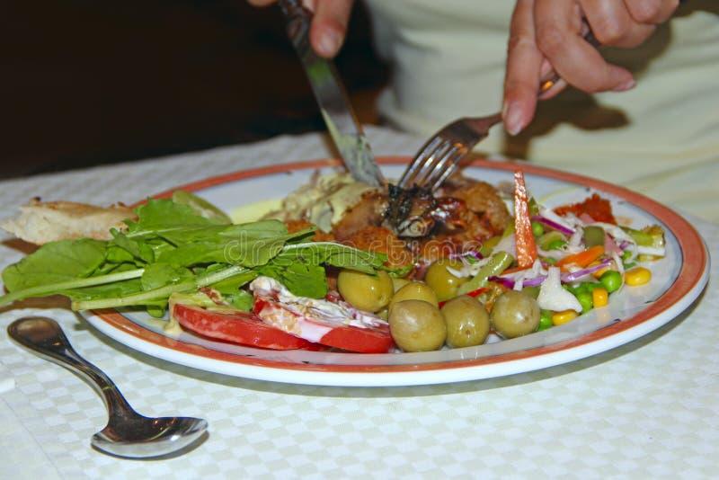 Mänskliga händer med gaffeln och kniven under att äta grönsaker och köttkroketten royaltyfri fotografi