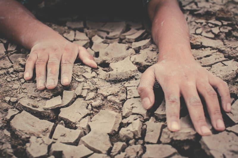 Mänskliga händer på sprucket torkar jordning royaltyfria foton