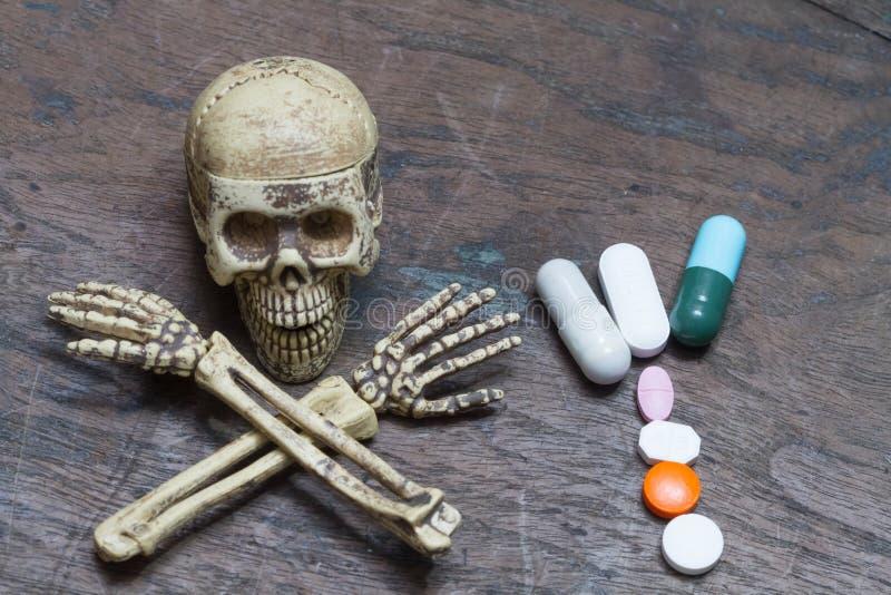 Mänskliga skalle och preventivpillerar på gammal wood bakgrund, sund omsorgconce arkivfoton