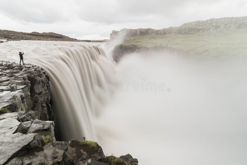 Mänskligt diagram anseende på klippkanten bredvid den Dettifoss vattenfallet i den Vatnayokull nationalparken, Island royaltyfri fotografi