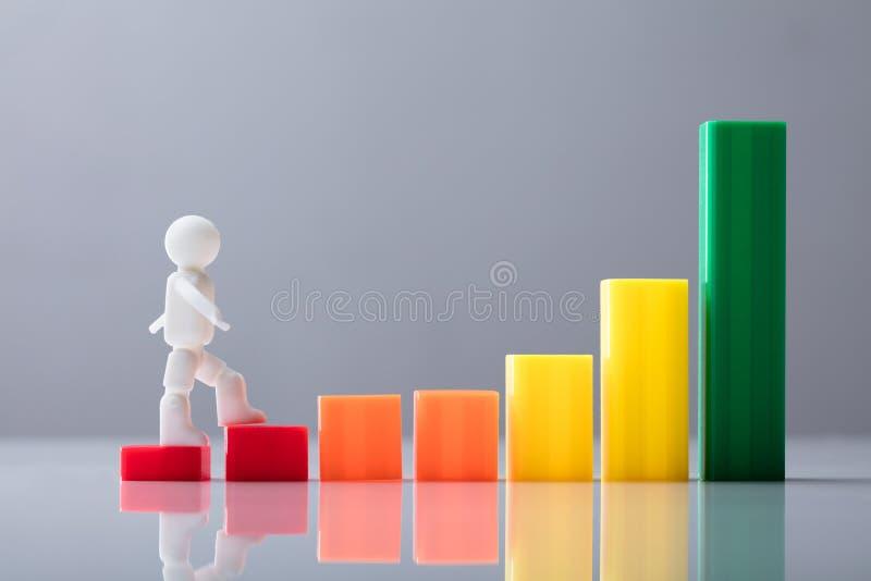 Mänskligt diagram som går på ökande affärsgraf arkivbilder