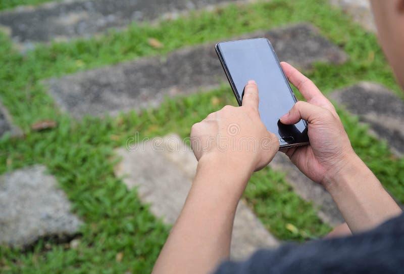 Mänskligt fingerinnehav och smart telefon för pekskärm i hand med naturbakgrund royaltyfria bilder