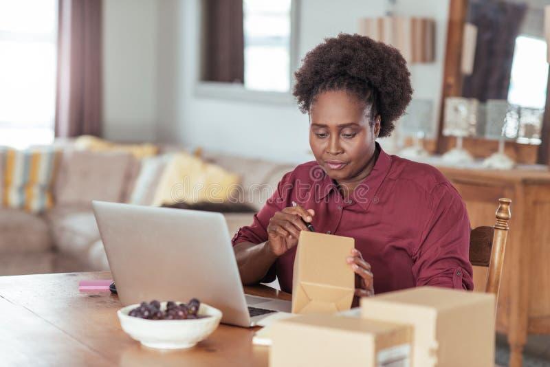 Märkande packar för ung afrikansk kvinna, medan arbeta hemifrån royaltyfria foton