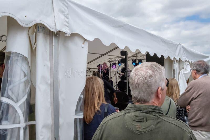 Märke för levande musik som spelar inom en stor stort festtält, medan medlemmar av allmänheten lyssnar utanför royaltyfri fotografi