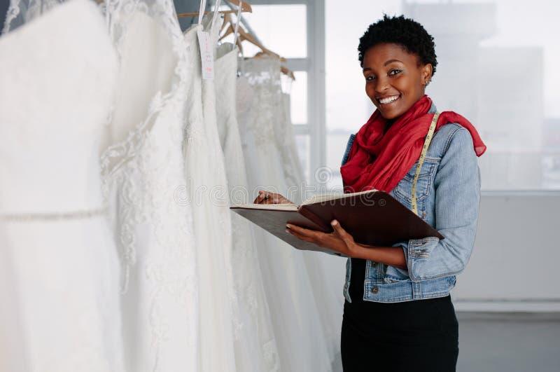 Märkes- arbete för kvinnliga brud- kläder i boutique arkivfoto