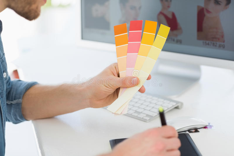 Märkes- arbete med det hållande färgdiagrammet för digitizer på hans skrivbord arkivbilder