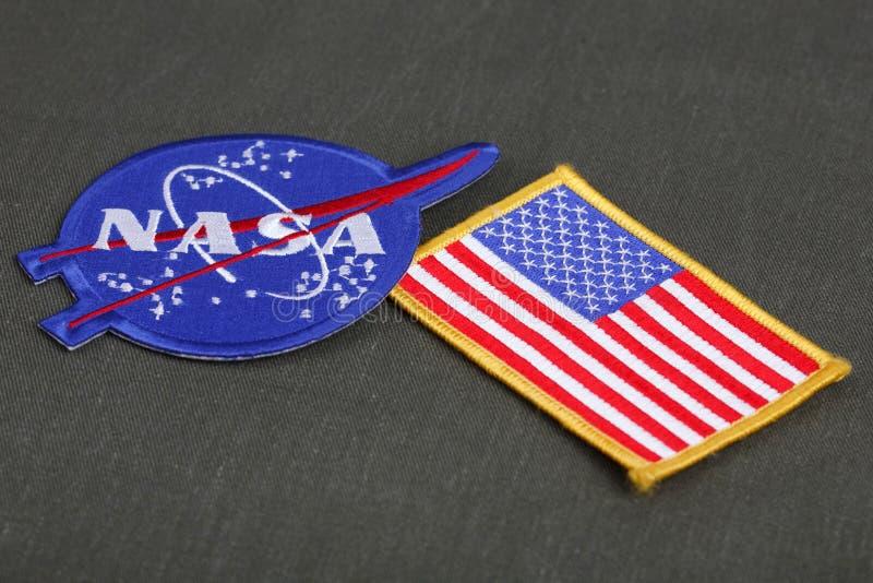 15. März 2018 - der Emblemflecken des National Aeronautics and Space Administration (die NASA) und US-Flaggenflecken auf grüner U stockfoto
