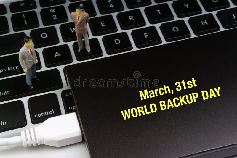 31. März schriftliche Wörter WELTder ersatztagesaufschrift, Laptop, Festplattenlaufwerk und Geschäftsmannminiatur lizenzfreie stockfotografie