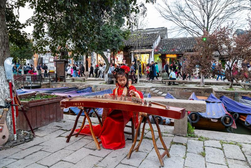 """März 2017 - Tongli, †Jiangsus, China """"Mädchen in einem traditionellen chinesischen roten Kleid, das ein Guzheng entlang den Kan stockbild"""