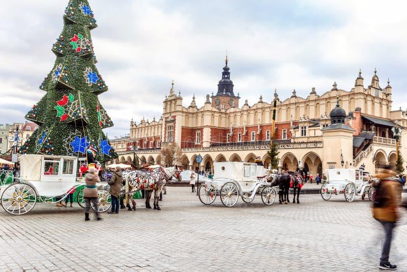 Mässa i Krakow Huvudsaklig marknadsfyrkant och Sukiennice i aftonen royaltyfria foton