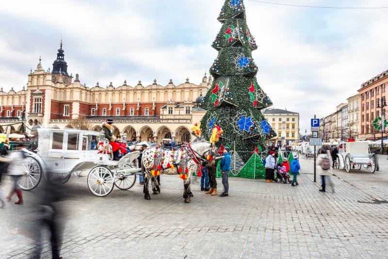 Mässa i Krakow Huvudsaklig marknadsfyrkant och Sukiennice i aftonen royaltyfri bild