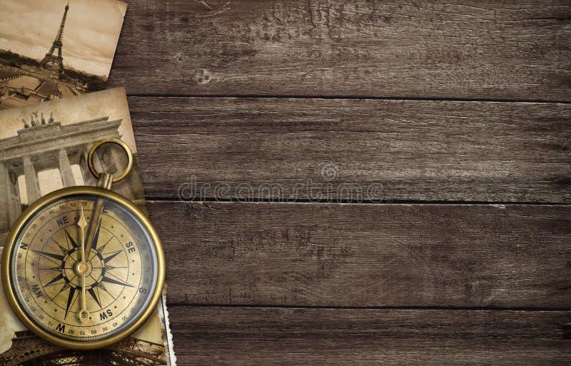 Mässingsantik kompass med gammala vykort arkivfoton