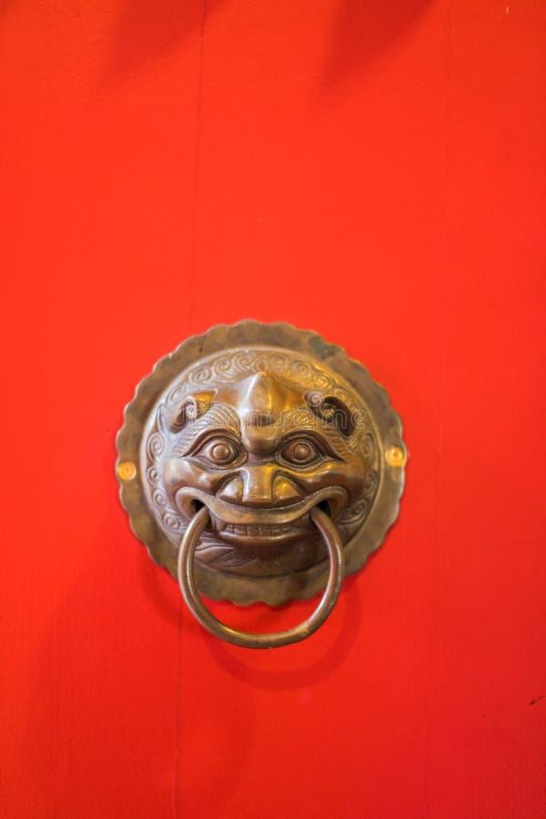 Mässingsdörrknackare på den röda dörren av templet royaltyfri bild