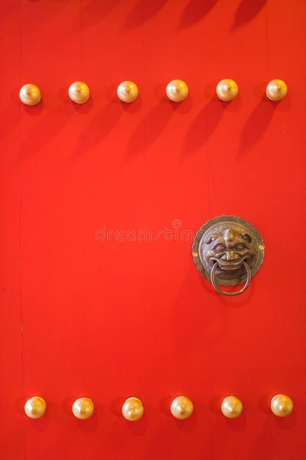 Mässingsdörrknackare på den röda dörren av templet royaltyfri foto