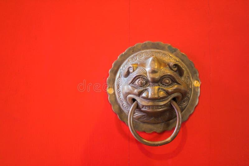Mässingsdörrknackare på den röda dörren av templet fotografering för bildbyråer